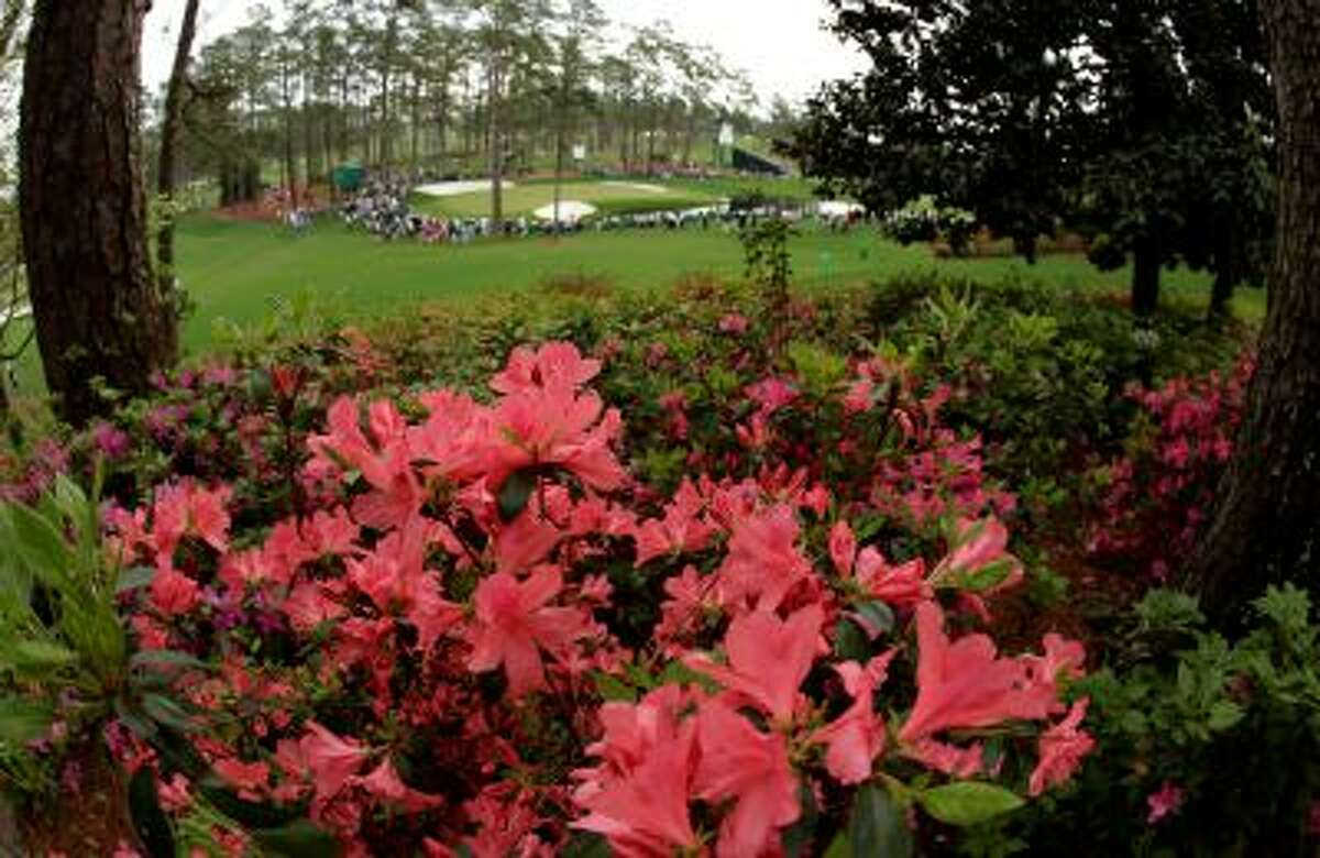 Azaleas bloom on the Augusta National Golf Course overlooking the 16th green during a practice round for the Masters golf tournament Tuesday, April 8, 2014, in Augusta, Ga. (AP Photo/Charlie Riedel)