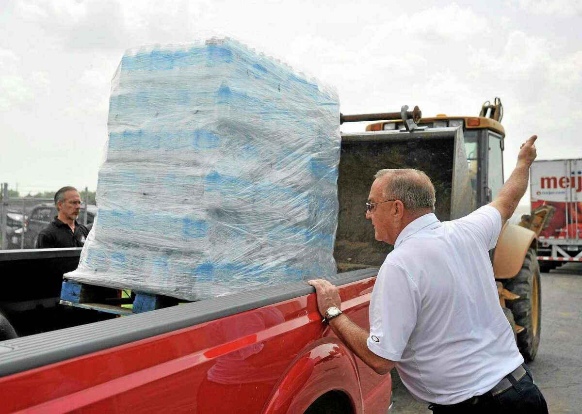 Monroe County, Michigan, Administrator and CFO Michael Bosanac, left, and Luna Pier, Mich., Mayor Dave Davison oversee a pallet of water, donated by a Meijer supermarket, being put into a truck to take to the Luna Pier fire station for distribution to the public, in Luna Pier, Mich., on Aug. 3, 2014. Four Monroe County communities have been told to to not use their water due to toxins in the Toledo water distribution system. (AP Photo/Detroit News, Robin Buckson) DETROIT FREE PRESS OUT; HUFFINGTON POST OUT MANDATORY CREDIT