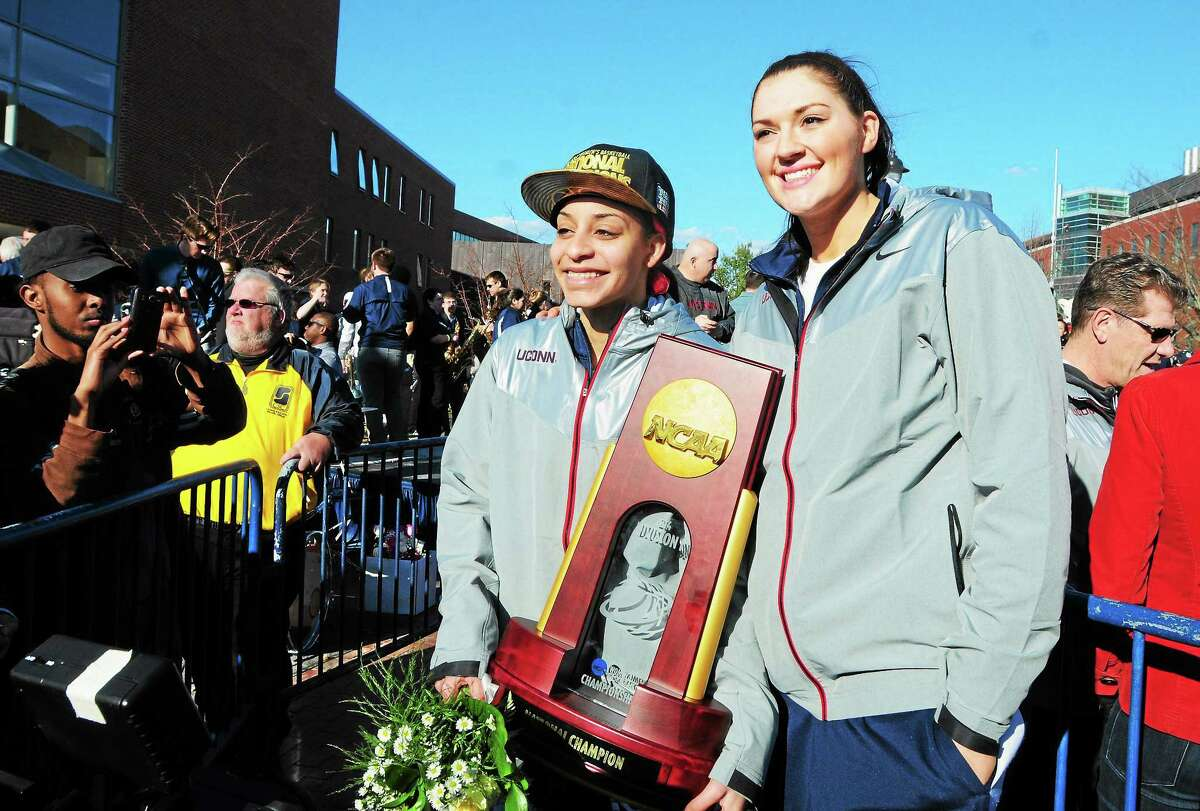 University of Connecticut seniors Bria Hartley, left, and Stefanie Dolson holding the NCAA Championship trophy pose for fans as the UConn women's basketball team is welcomed back in Storrs Wednesday after the team won its ninth national championship title Tuesday night against Notre Dame.