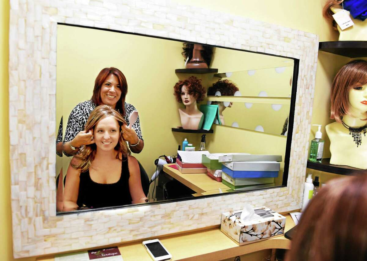 (Peter Hvizdak - New Haven Register) Andrea M. Torre of Wallingford, a licensed Cosmetologist and certified wig specialist at the Smilow Cancer Hospital at Yale-New Haven in the Cingari Family Boutique in New Haven, Connecticudt as the hospital's hairdresser, provides a wig consultations and fittings to cancer patient Ana Griffin of Fairfield, as she tried, and was fitted for, various styles of wigs by Ms. Torre Tuesday, August 5, 2014
