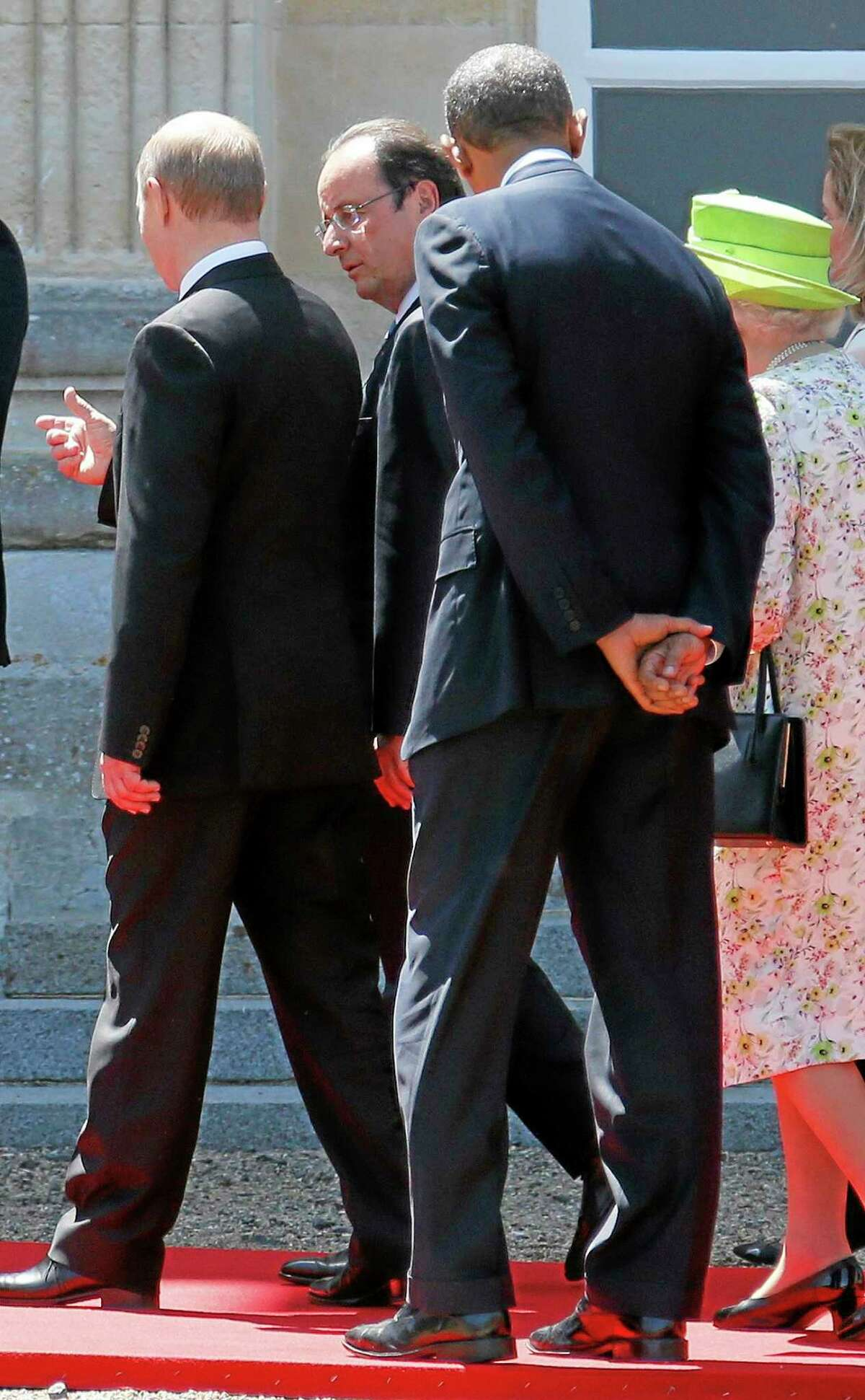 Russian President Vladimir Putin, left, talks to French President Francois Hollande, 2nd left, as they walk next to U.S. President Barack Obama, 2nd right and Britain's Queen Elizabeth after posing for a group photo for the 70th anniversary of the D-Day landings at Benouville castle, in Normandy, France, Friday, June 6, 2014. World leaders and veterans paid tribute on the 70th anniversary of the World War Two D-Day landings to soldiers who fell in the liberation of Europe from Nazi German rule, as host France sought to use the event to achieve a thaw in the Ukraine crisis. (Regis Duvignau, pool)