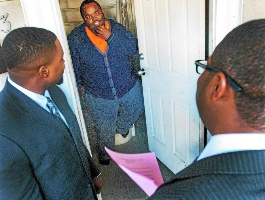 Malcolm Welfare, left, Youth Leadership Coordinator for New Haven Public Schools, and Quavon Newton, right, Youth Minister for Varick Memorial A.M.E. Zion Church, give an information packet to Quashon Williams as they canvass the Dixwell neighborhood reaching out to youths Wednesday in the city. Photo: Melanie Stengel — New Haven Register