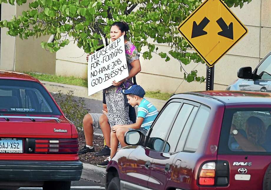 A woman stands with a sign off the Boston Post Road in Milford Tuesday. Photo: Melanie Stengel  New Haven Register