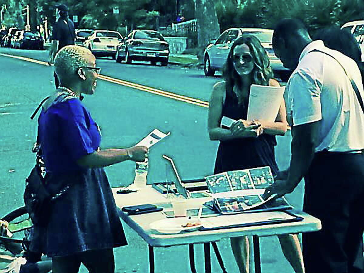 Latoi Smith, Dir. of Volunteer Services for Bereavement Care Network, with fliers at Orchard St. National Night Out.