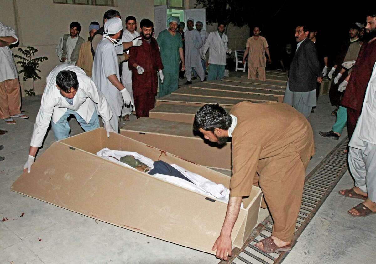 Medics close a coffin of a person killed from a roadside bomb in Kandahar, south of Kabul, Afghanistan, Monday, April 7, 2014. A roadside bomb killed at least 15 people traveling in vehicles that had been diverted from a main road Monday after an earlier attack in southern Afghanistan, officials said. (AP Photo/Allauddin Khan)
