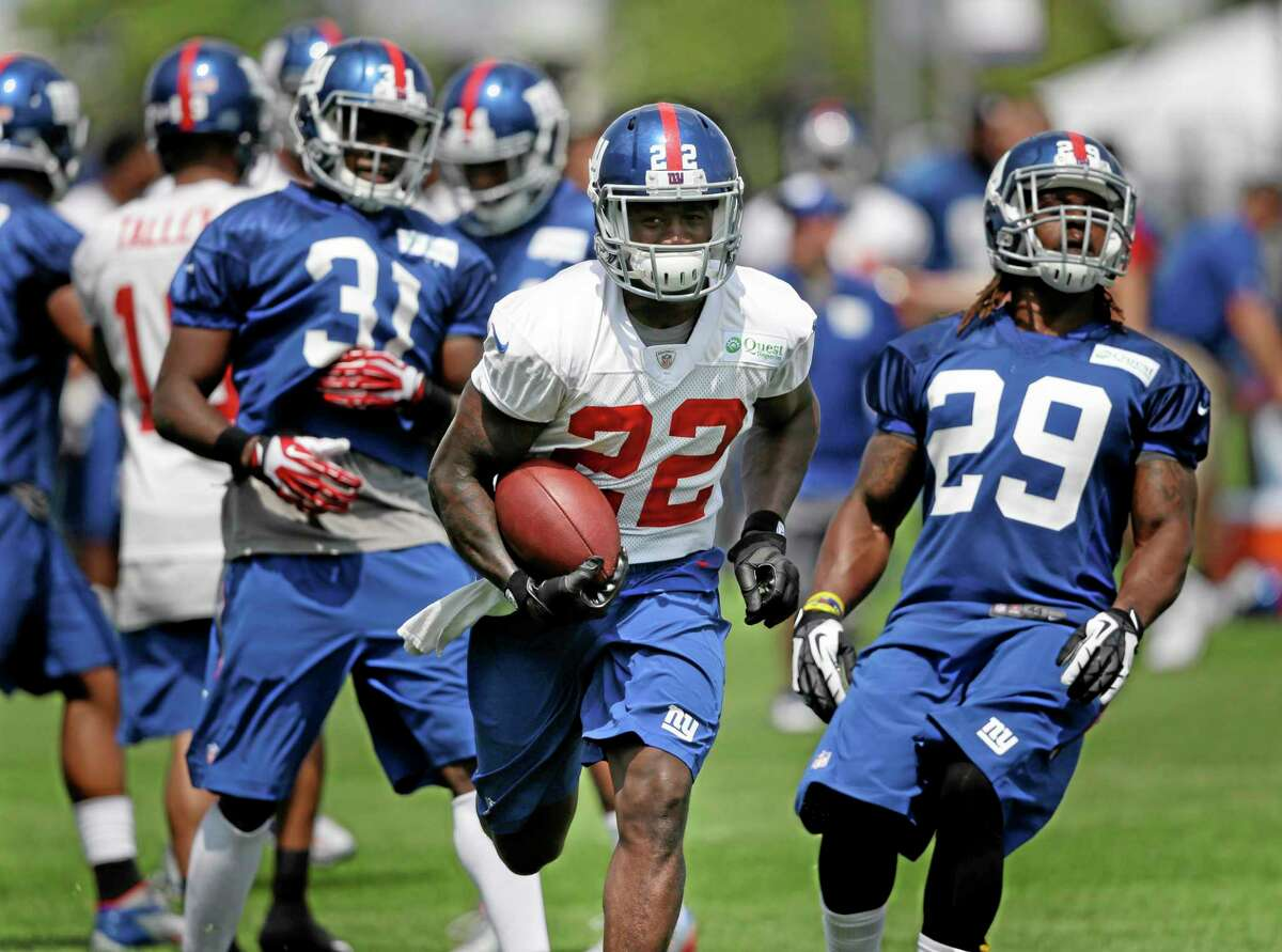 New York Giants' David Wilson runs with the ball during NFL football camp in East Rutherford, N.J., Tuesday, July 22, 2014. (AP Photo/Seth Wenig)
