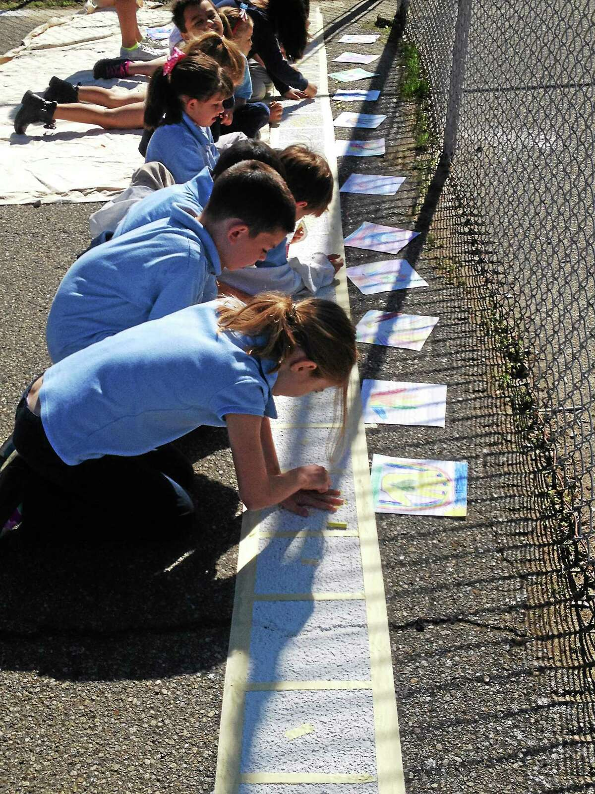 Students at John G. Prendergast school work on creating a border for a new play area.