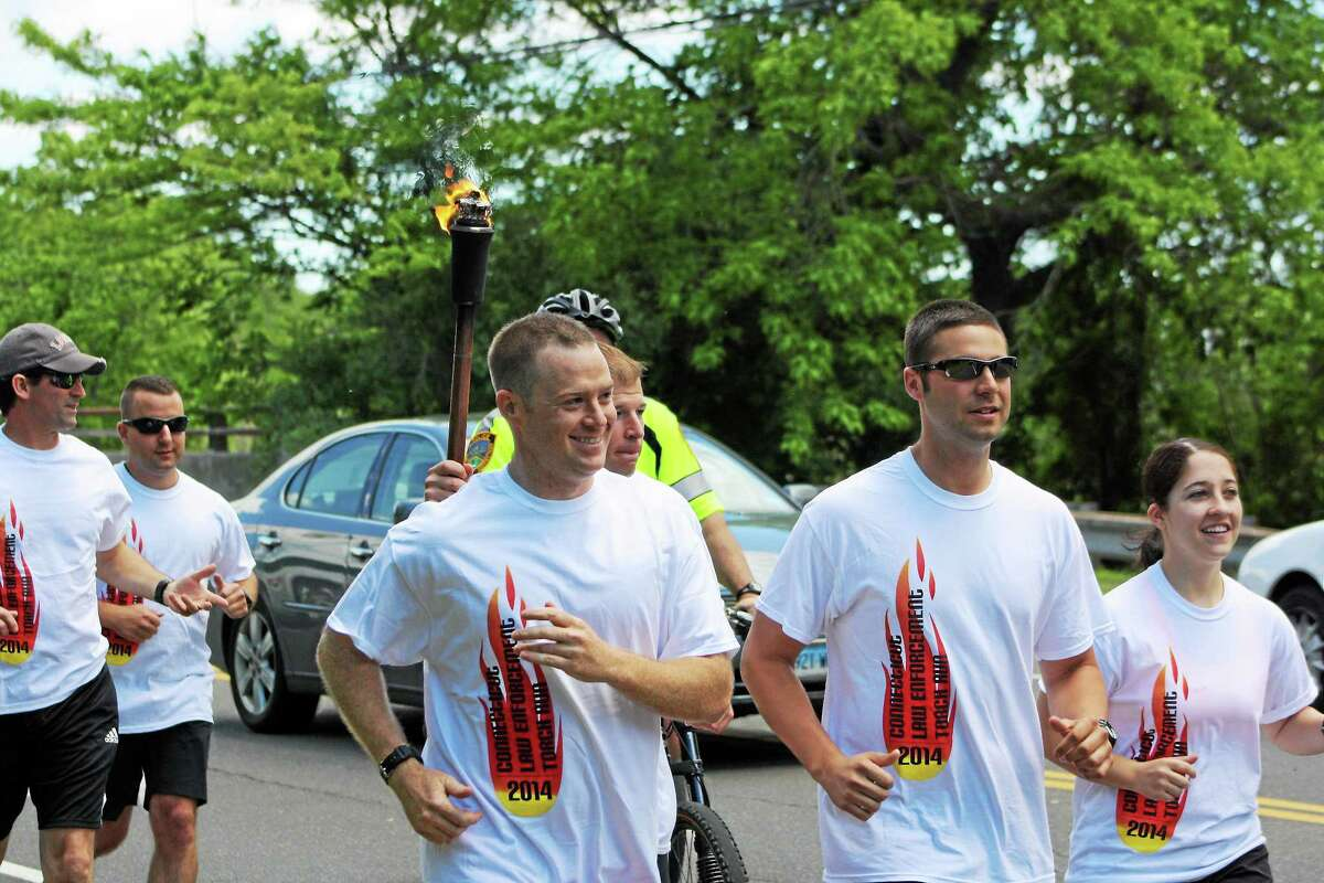 With Guilford Officer Rich Casey holding up the torch, fellow town officers run for Special Olympics.
