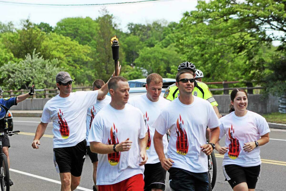 Two Madison police officers run down Boston Post Road with the torch.