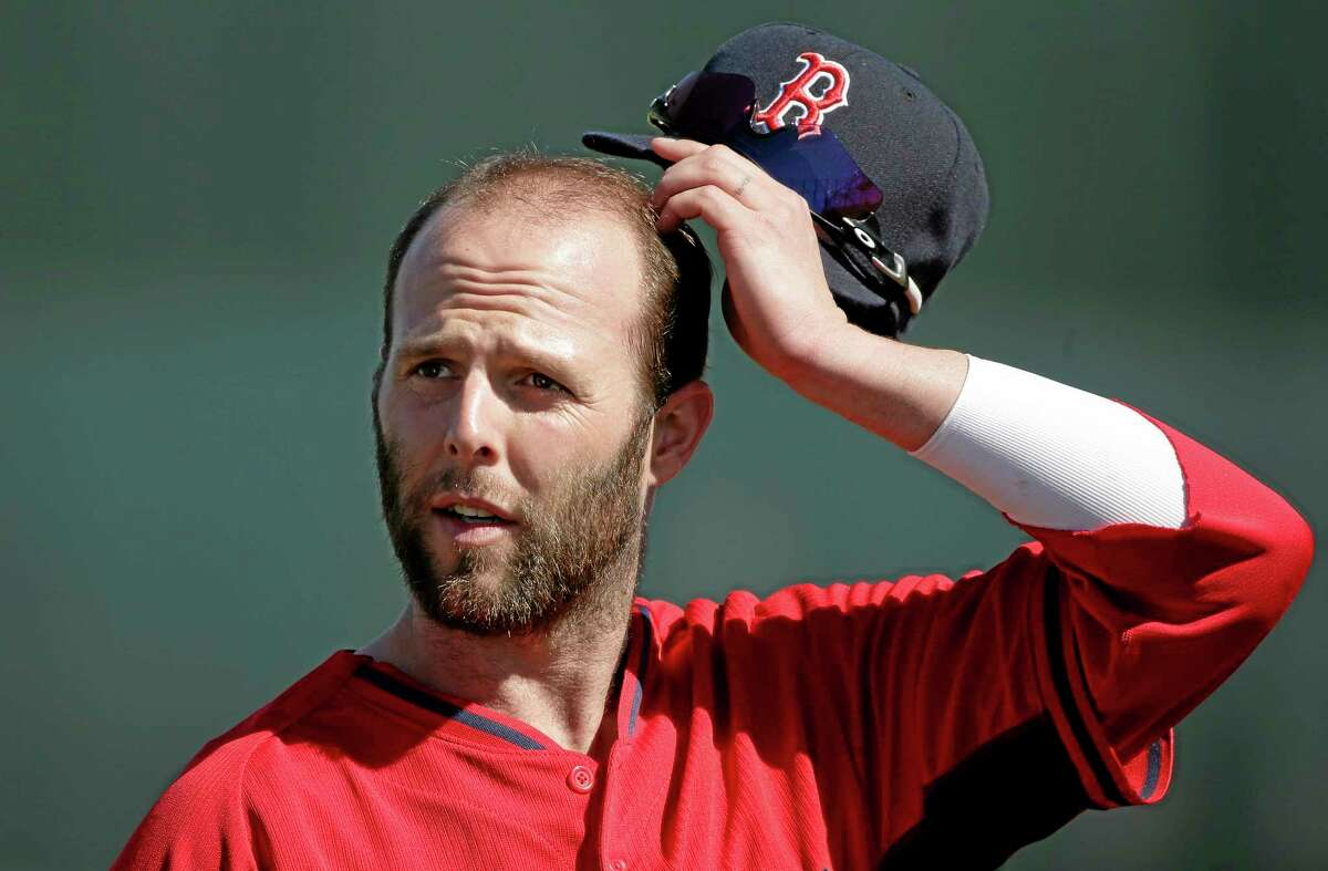 Red Sox second baseman Dustin Pedroia removes his hat during practice Monday in Fort Myers, Fla.