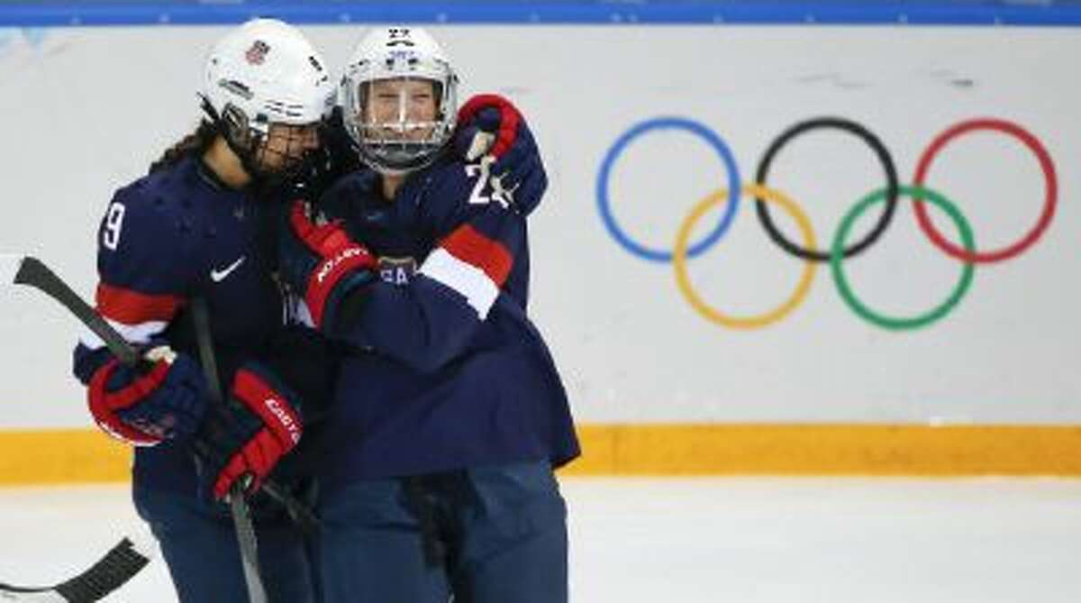 Megan Bozek of the United States, left, congratulates teammate Kacey Bellamy after Bellamy scored a goal against Sweden during the first period of the 2014 Winter Olympics women's semifinal ice hockey game at Shayba Arena Monday, Feb. 17, 2014, in Sochi, Russia.
