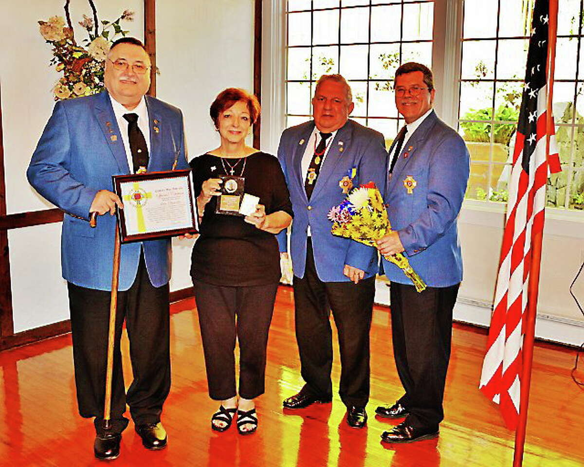"""Photo by: Markanthony Izzo DERBY >> Ann Donato of Oxford holds an award and a white cross presented at the Department of Connecticut Catholic War Veterans state convention held recently att St. Michael's Post 1562, Derby. With Donato, from left, are Post 1562 Cmdr. Tom Voytek, holding Donato's citation; Department of Connecticut Cmdr. Michael Ranno, and convention chairman Michael Kasinskas, with flowers for Donato. Donato was given the department's first Patriotic Citizen Award for her support of U.S. troops in Afghanistan's remote areas of operation. Donato has packaged and mailed 1,805 """"care"""" packages since 2006. At the convention, she displayed five binders of thank-you letters, citations and kind words from the troops who received her packages, and gave a brief history of her """"Support Our Troops"""" program. """"They are my heroes and our guardians of America,"""" she said. Tom Voytek praised Donato as """"one of God's messengers doing the Lord's work."""" For details on Donato's program, call Post 1562 at 203-734-9748."""