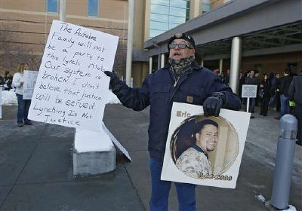 """Bob Autobee holds a picture of his son Eric as he protests against the death penalty at the courthouse in Castle Rock, Colo. The father of a prison guard killed more than a decade ago, Autobee says he sees """"hope and conversion"""" in the inmate accused of killing his son and doesn't want him executed."""