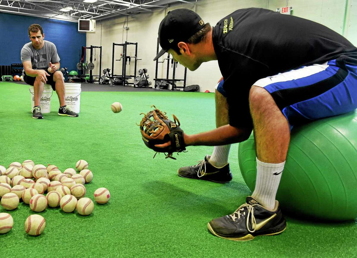 Coach Matt Untiet, left, an employee of The Grind, and Jake Russo, 17, of Orange, practice a fielding drill at the Grind Baseball and Softball training facility in Orange.