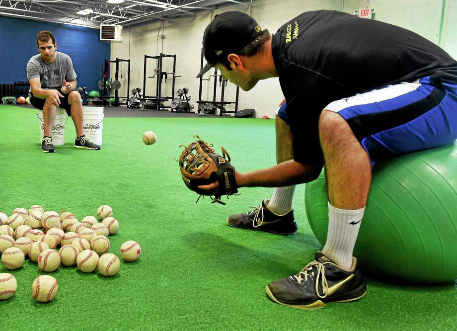 Coach Matt Untiet, left, an employee of The Grind, and Jake Russo, 17, of Orange, practice a fielding drill at the Grind Baseball and Softball training facility in Orange. Photo: Peter Hvizdak — Register   / ©Peter Hvizdak /  New Haven Register