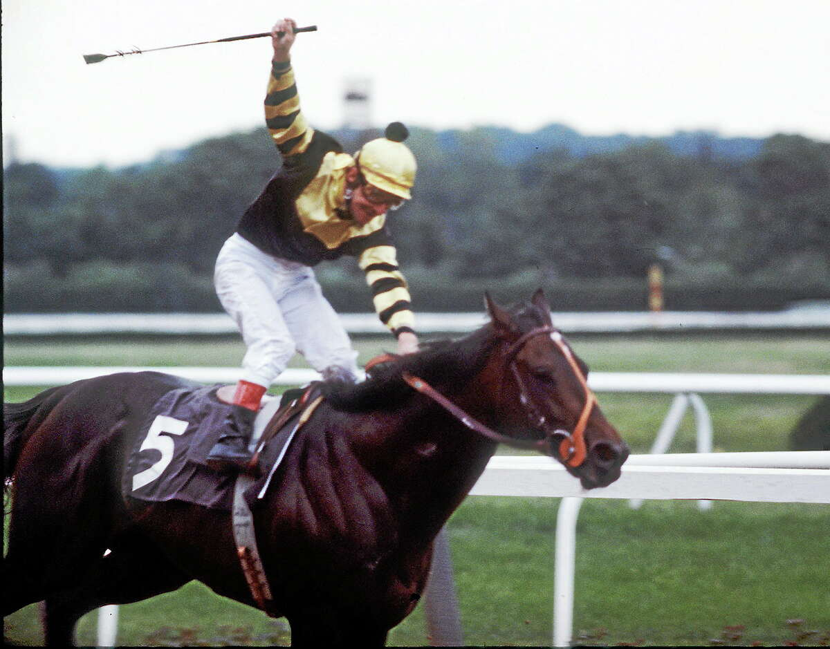Jockey Jean Cruget stands up in his saddle and celebrates after guiding Seattle Slew to victory in the Belmont Stakes at Belmont Park in Elmont, N.Y. on June 11, 1977. The win gives Slew horse racing's Triple Crown.