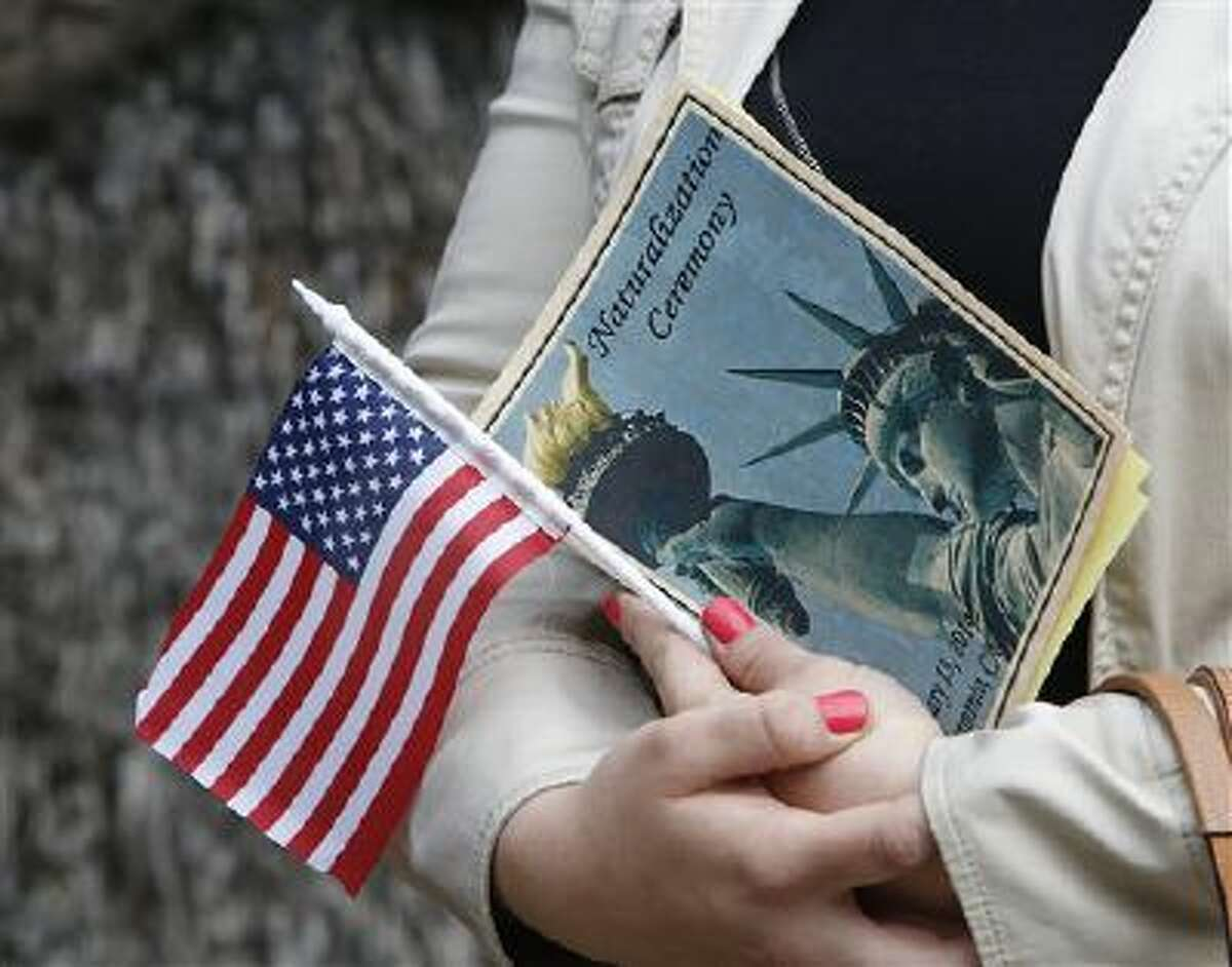 Kristina Drobot holds an American flag as she waits to be sworn-in as a U.S. citizen during naturalization ceremonies in Sacramento, Calif. Drobot, 23, who immigrated from Russia, was among 15 people from nine countries who took the oath of citizenship in time for the Presidents Day weekend.