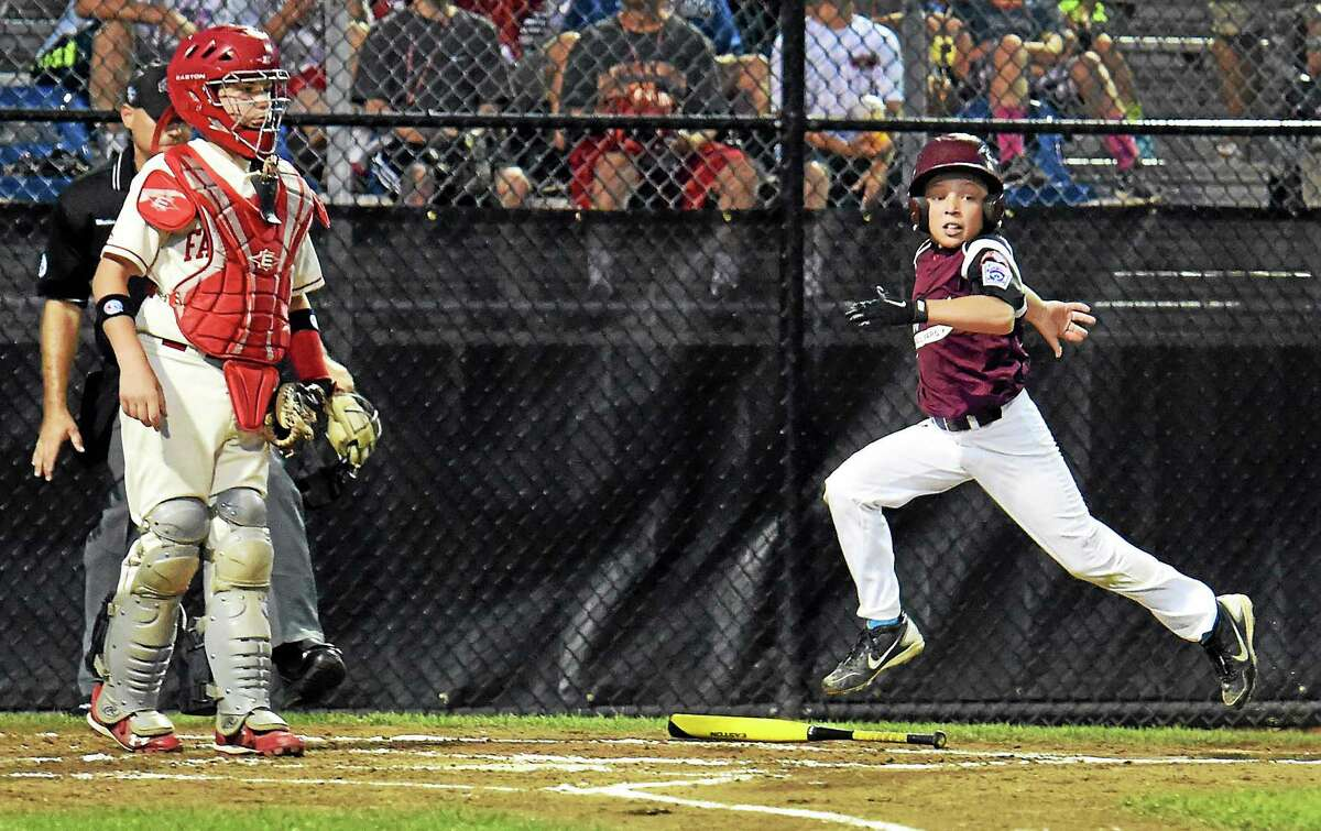 Vince Camera of Fairfield American watches as Brad Demers of Goffstown (New Hampshire) scores in the second inning Sunday.