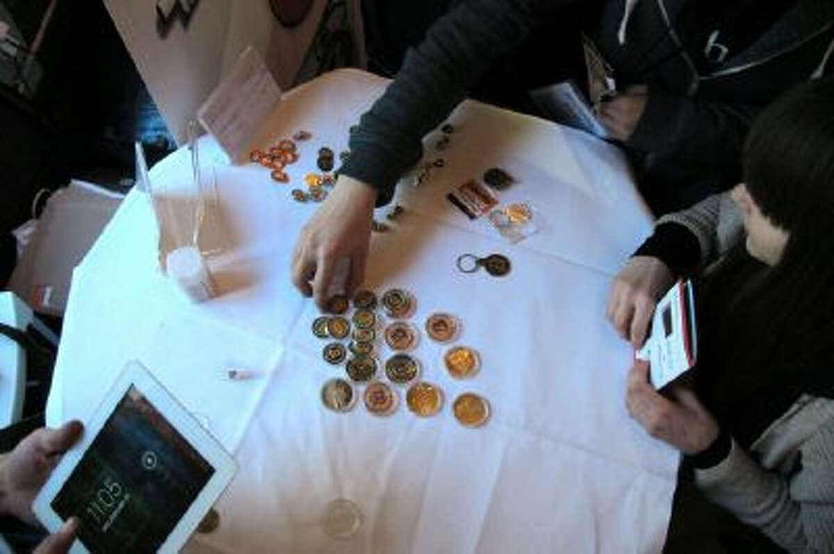 Attendees of the Inside Bitcoins conference in Berlin examine Bitcoin buttons on Wednesday, Feb. 12, 2014.