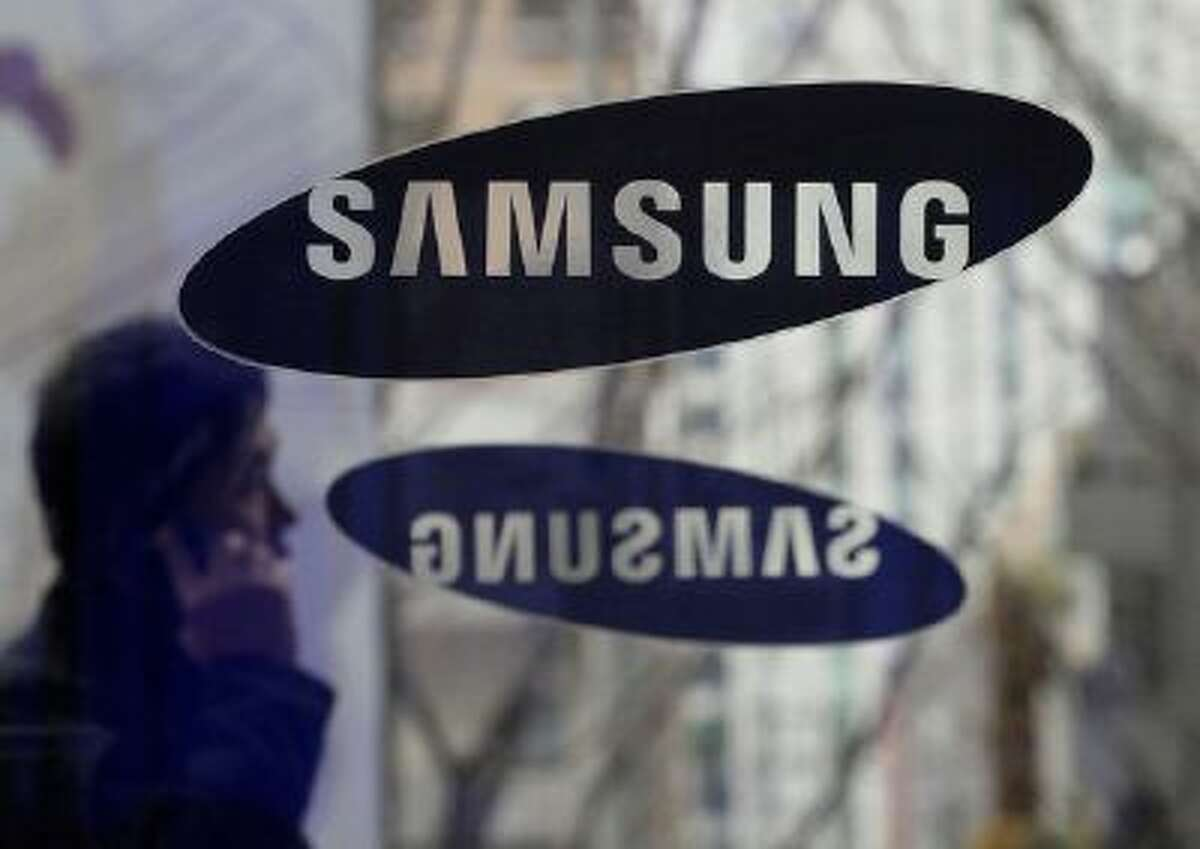 File - In this Dec. 12, 2013 file photo, a man passes by the Samsung Electronics Co. logos at its headquarters in Seoul, South Korea. Opening statements are underway in the latest patent fight over mobile devices between Apple and Samsung, the world's largest cellphone manufacturers. An Apple lawyer told jurors in San Jose, Calif., on Tuesday April 1, 2014, that Samsung quickly recognized that the iPhone was going to be a big seller when it first went on the market, and the South Korean company didn't have a product that could compete. (AP Photo/Ahn Young-joon, File)