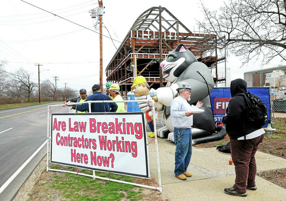 Members of the New England Regional Council of Carpenters picket Monday next to the construction site of an academic and laboratory building at Southern Connecticut State University in New Haven.