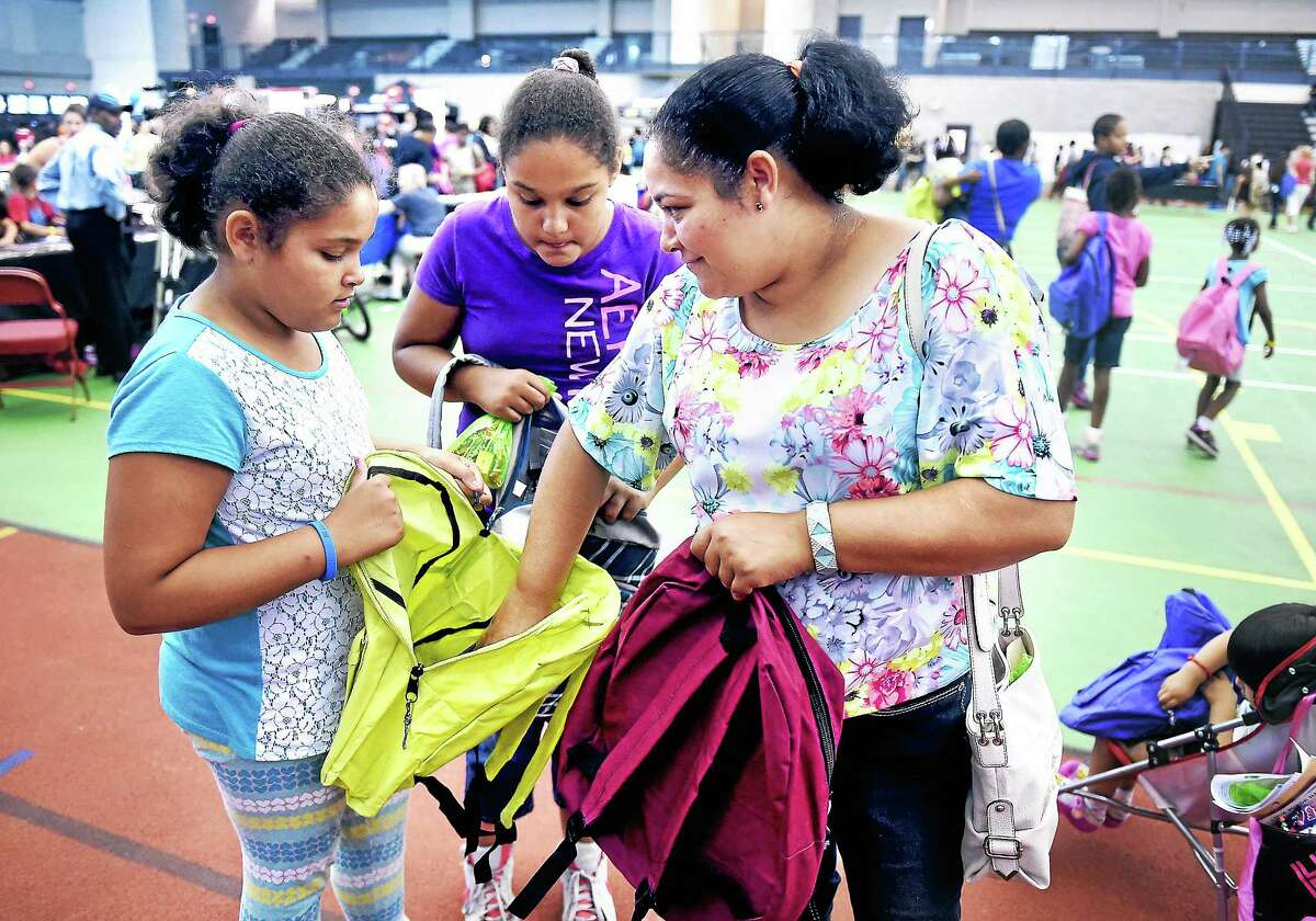 Angie Nieves (left), 9, and her sister, Marleny (center), 11, look over their new backpacks with their mother, Francisca (right), at the Back to School Rally at the Floyd Little Athletic Center in New Haven on August 2, 2014.