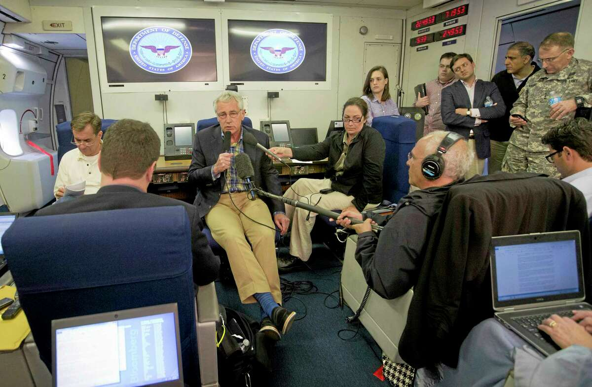U.S. Defense Secretary Chuck Hagel, center, is seen aboard a U.S. Military Aircraft before speaking to members of the media during his flight, Sunday, June 1, 2014. Hagel spoke about the released of U.S. Army Sgt. Bowe Bergdahl who was held hostage in Afghanistan, and who was handed over Saturday morning by members of the Taliban in exchange for five Afghan detainees held at the military prison in Guantanamo Bay prison in Cuba.