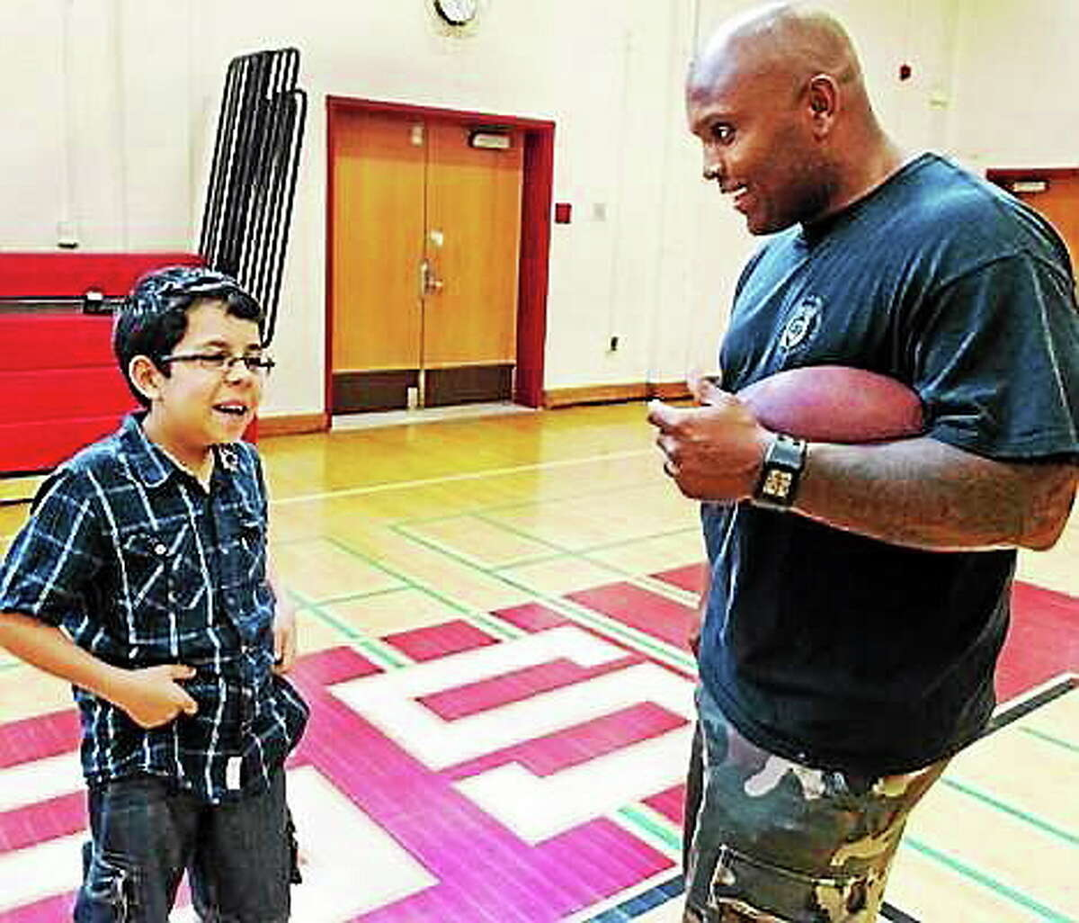 File photo: Melanie Stengel/New Haven Register Alex Rivera, 12, left, and New Haven Police Officer Charles Tyson talk at the start of New Haven police P.A.L. Camp 2013.
