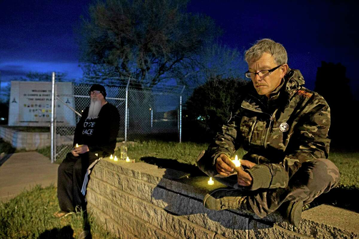 """Army veterans David Bass, left, Michael Clift participate in a candlelight vigil for the victims of Wednesday's shooting at Fort Hood, at the East Gate of the Texas military base, on Friday, April 4, 2014. The Fort Hood soldier who gunned down three other military men before killing himself had an argument with colleagues in his unit before opening fire, and investigators believe his mental condition was not the """"direct precipitating factor"""" in the shooting, authorities said Friday."""