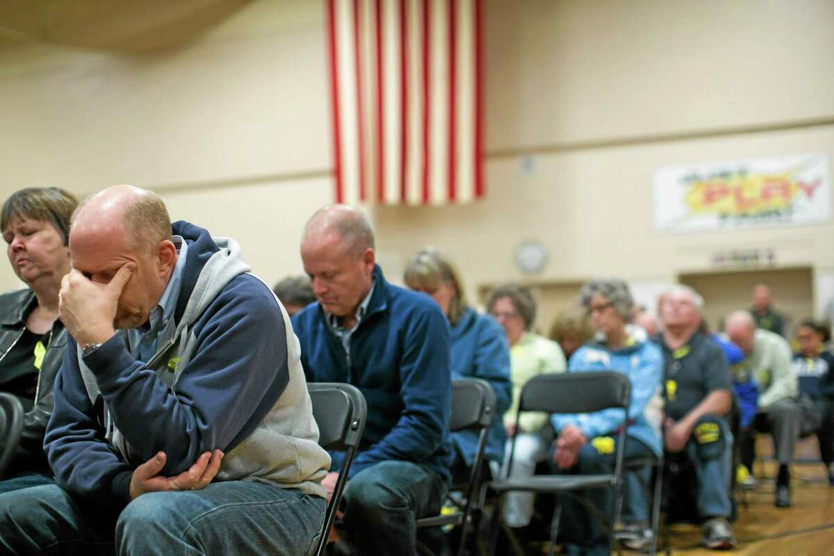 """Residents bow their head in prayer as they attend a prayer service dedicated to the communities affected by the Highway 530 mudslide, during the """"Together Evening of Prayer"""" at Haller Middle School in Arlington, on Friday, April 4, 2014. (AP Photo/POOL, Marcus Yam)"""