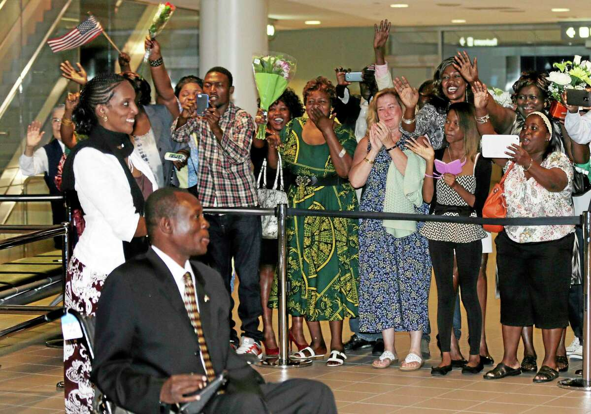 Meriam Ibrahim, left, and her husband, Daniel Wani, of Sudan, are greeted by family and friends shortly after arriving in Manchester, N.H., Thursday, July 31, 2014. Ibrahim, who refused to recant her Christian faith in the face of a death sentence that was later overturned, will make their new home in New Hampshire. (AP Photo/Charles Krupa)
