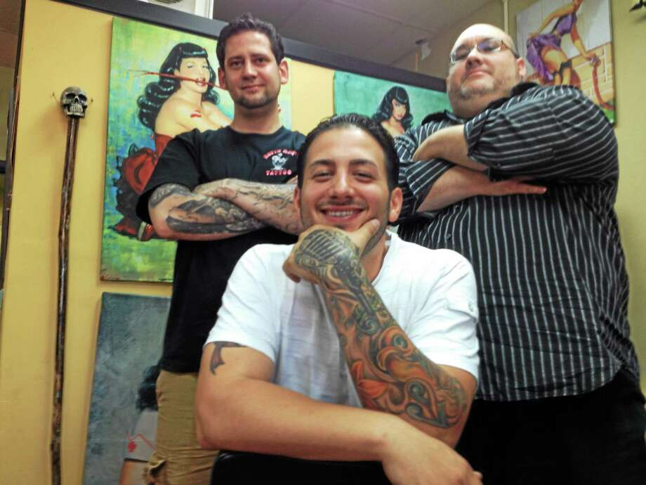 """The Voice"" candidate Michael Martone of West Haven, center, poses in Savin Rock Tattoo & Skate with owner and good friend Brian Christiani, left, who nominated him, and Omar Sanchez, drummer for The Mike and Mike Band, which Martone fronts. Photo: Mark Zaretsky — NEW HAVEN REGISTER"