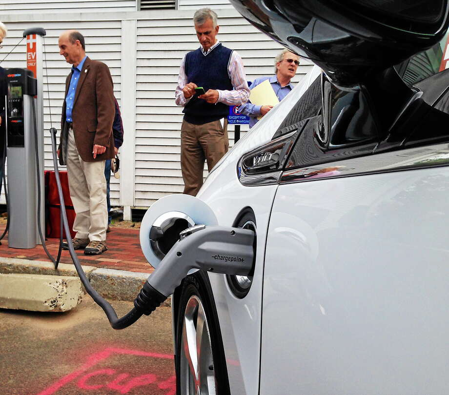 Madison officials demonstrate how the charging station works on a Chevy Volt. Photo: SEAN CARLIN — NEW HAVEN REGISTER