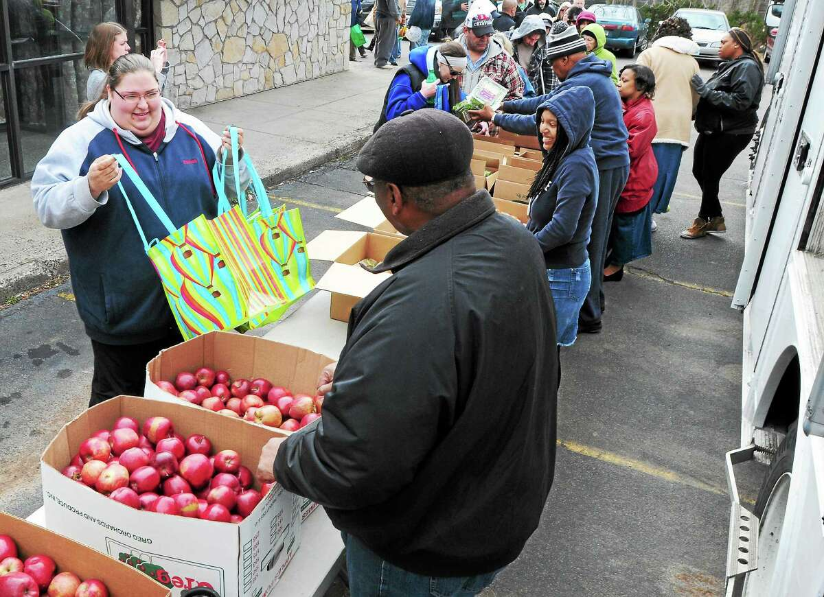 (Peter Hvizdak — New Haven Register) Jennifer Zacharie of Branford, 30, left, gets food from the Connecticut Food Bank mobile pantry truck Friday morning, April 4, 2014, at the New Life Apostolic Church in Branford.