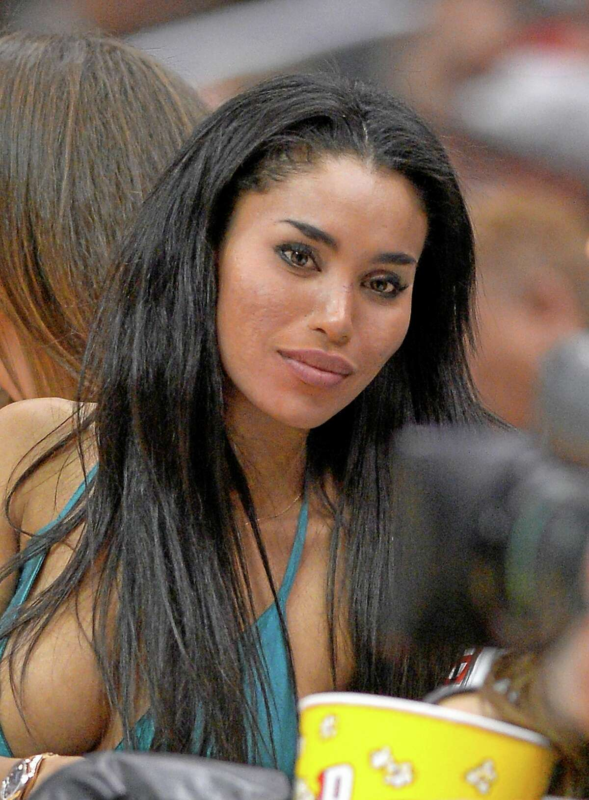 FILE - An Oct. 25, 2013, file photo is of V. Stiviano watching the Los Angeles Clippers play the Sacramento Kings during the first half of an NBA basketball game in Los Angeles. Stiviano, the woman Los Angeles Clippers owner Donald Sterling was talking to when he made racist remarks says she was assaulted by two men outside a New York City hotel Sunday June 1, 2014. (AP Photo/Mark J. Terrill)