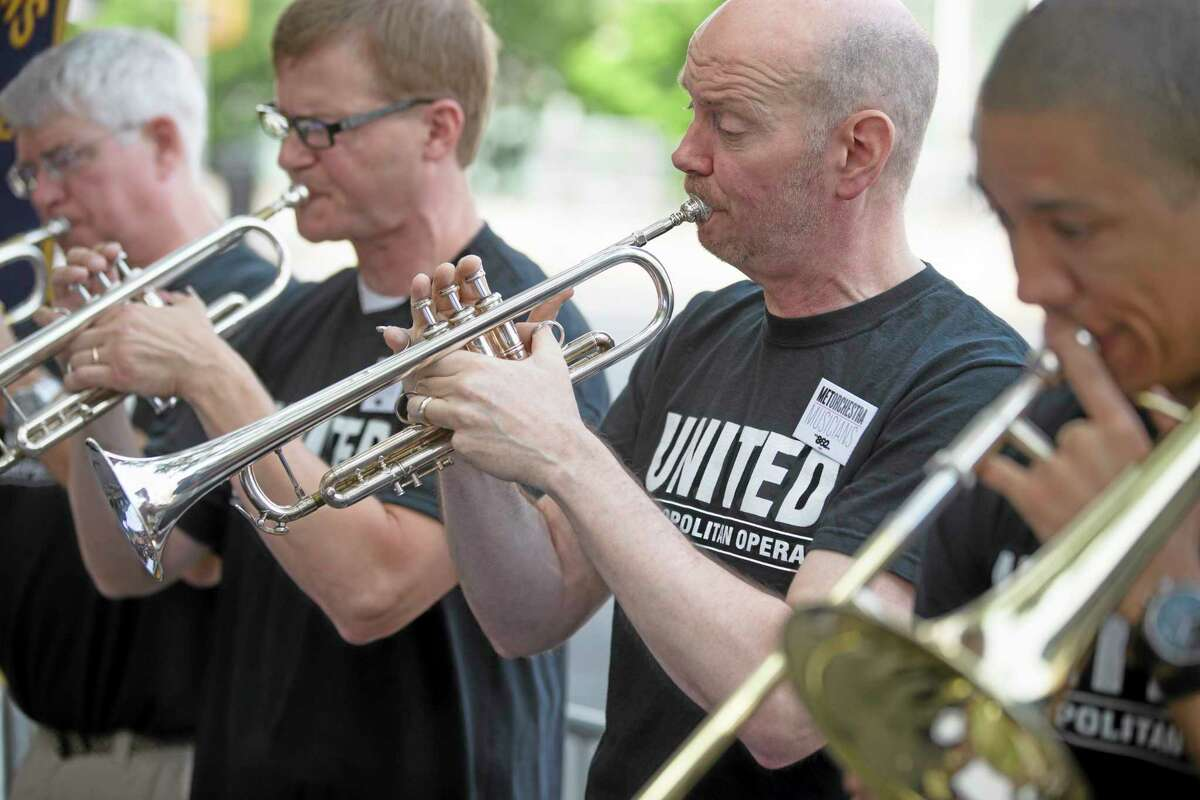 Demonstrators play their musical instruments outside Lincoln Center during a protest over a labor dispute with New York's Metropolitan Opera Friday in New York.