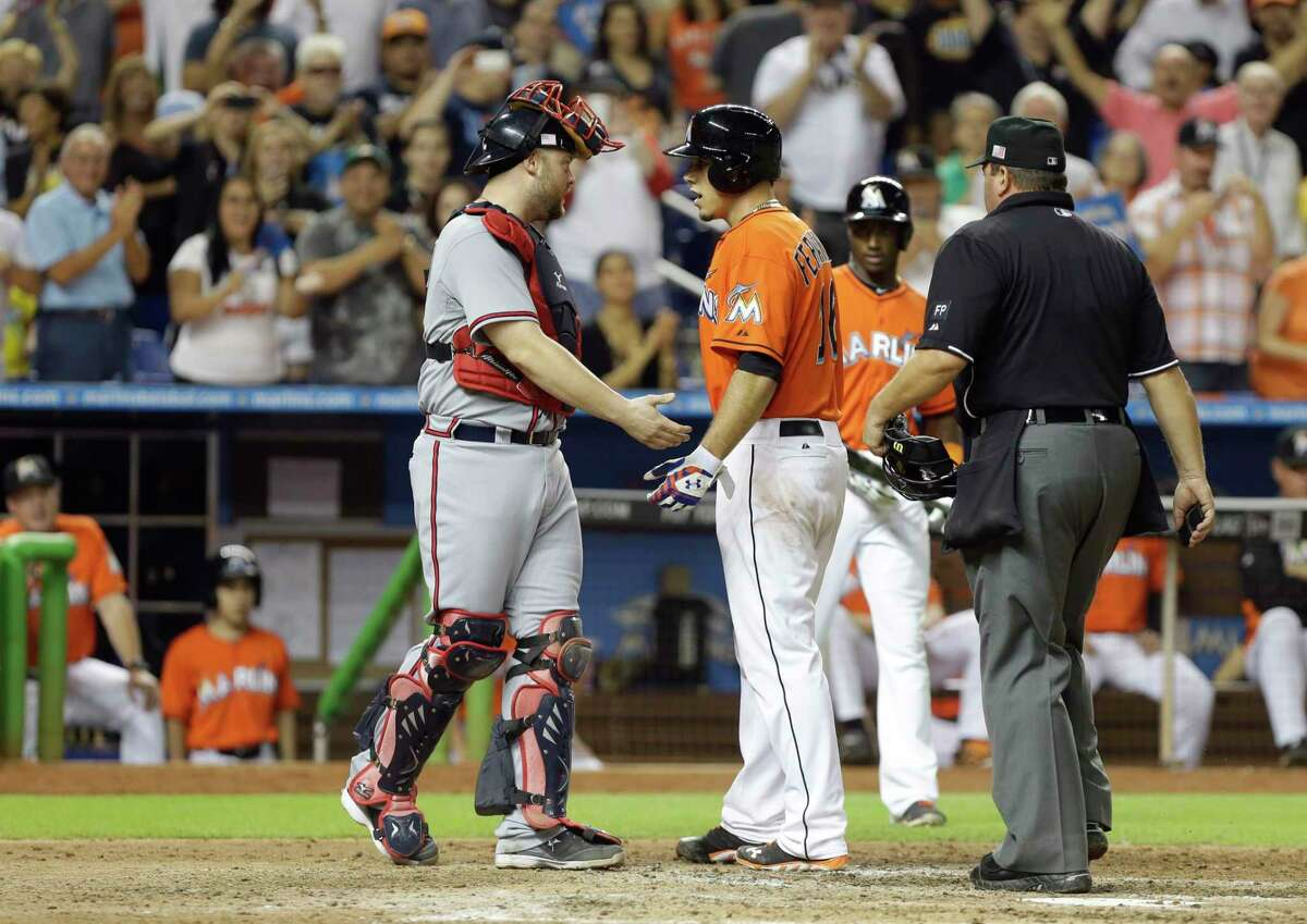 Atlanta Braves catcher Brian McCann, left, and Marlins pitcher Jose Fernandez exchange words after Fernandez hit a home run during a game Sept. 11, 2013, in Miami.