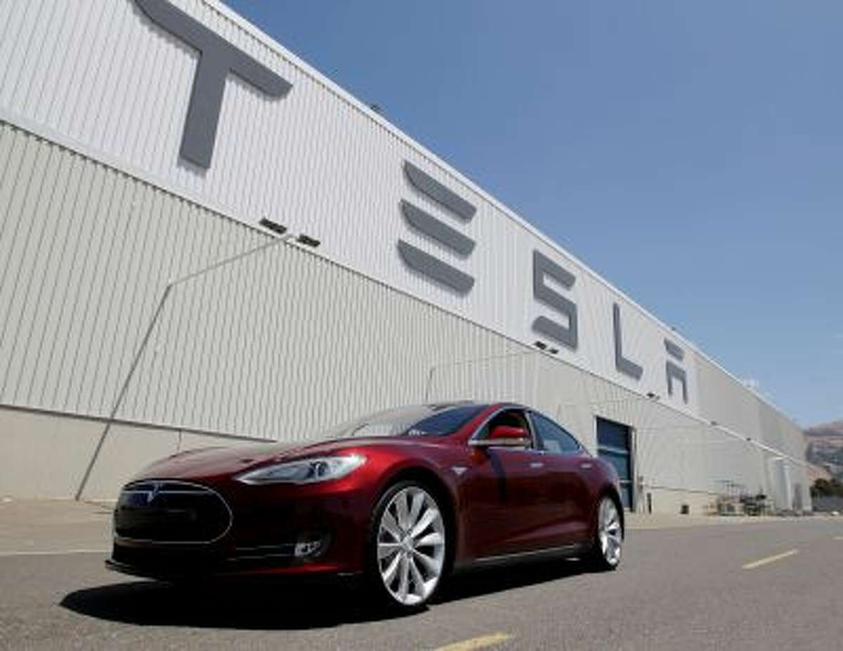 FILE - In this June 22, 2012 file photo shows a Tesla Model S driving outside the Tesla factory in Fremont, Calif. Shares of Tesla Motors are down another 5 percent as investors in the high-flying company assess the fallout from a fire in one of its $70,000 electric cars. (AP Photo/Paul Sakuma, file)