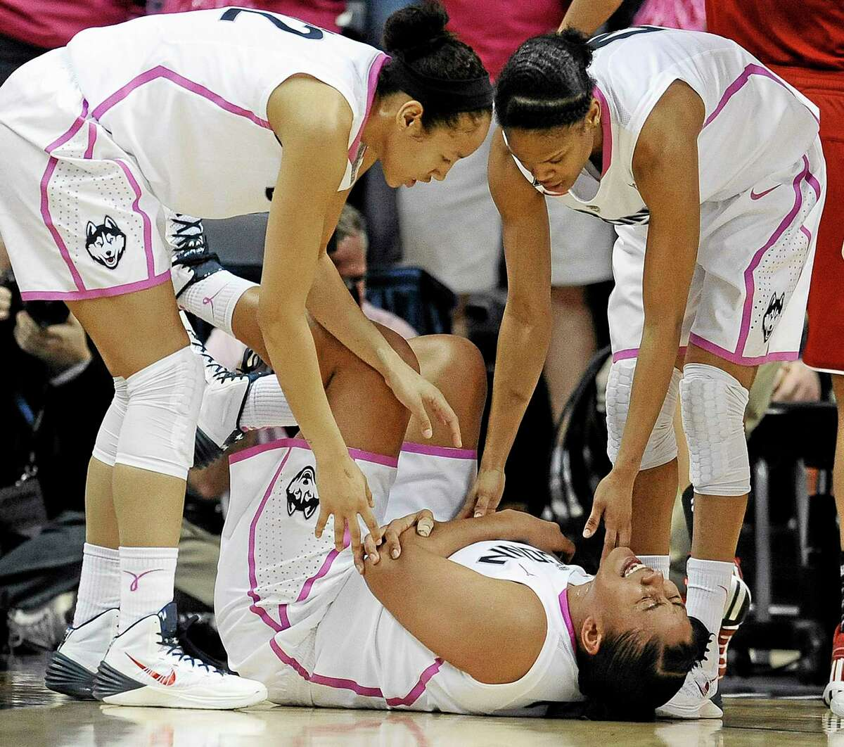UConn's Kaleena Mosqueda-Lewis holds her arm after a hard fall to the court as teammates Saniya Chong, left, and Moriah Jefferson, right, look over her during Sunday's game. The Huskies learned Friday that Mosqueda-Lewis will miss the next 3-6 weeks due to mononucleosis.