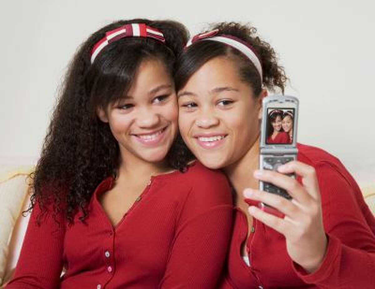African twin sisters taking own photograph