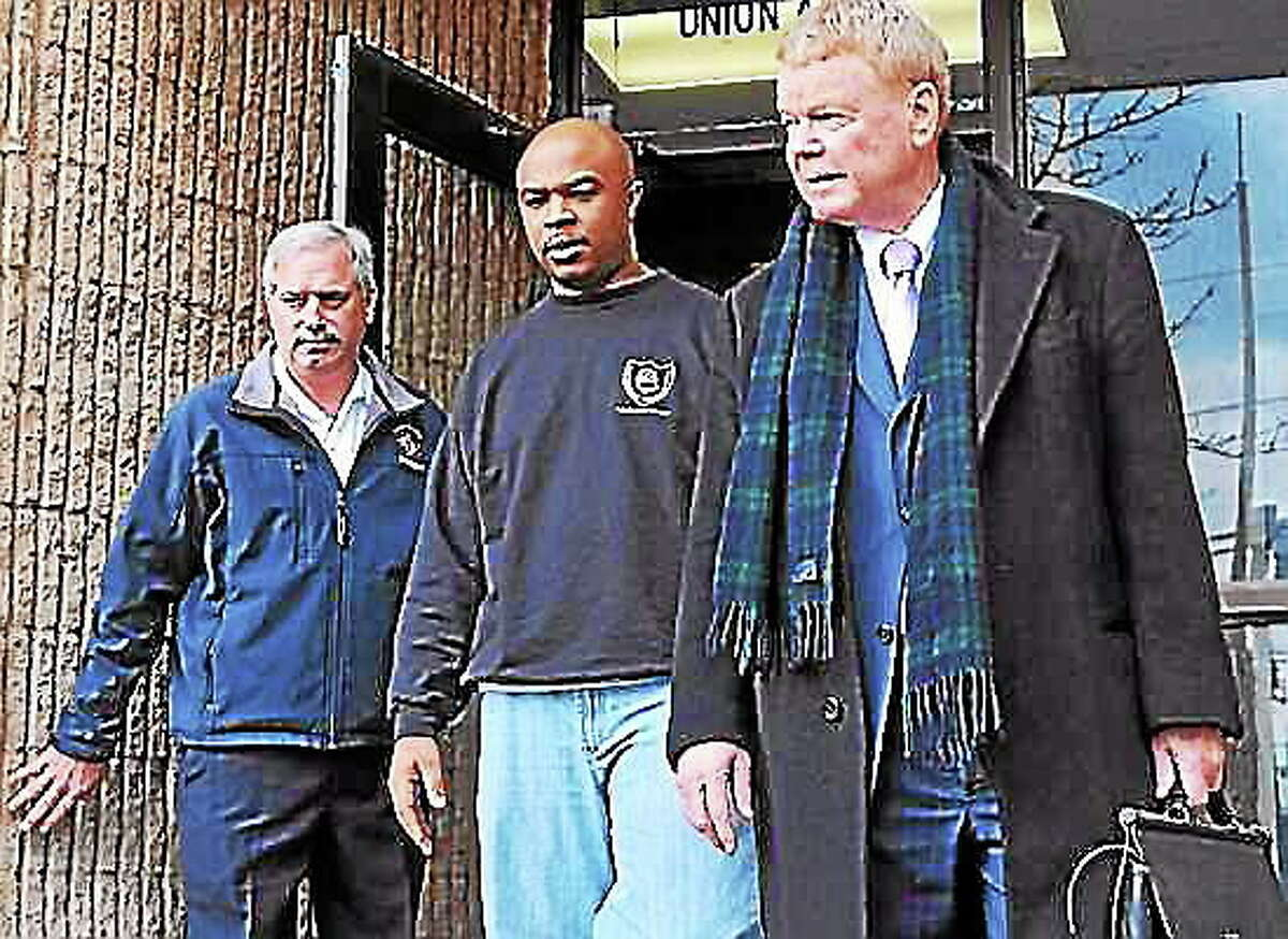File photo: New Haven Firefighter Aaron Brantley, center, leaves police headquarters with his attorney Hugh Keefe, right, and Lt. James Kottage, fire union president.