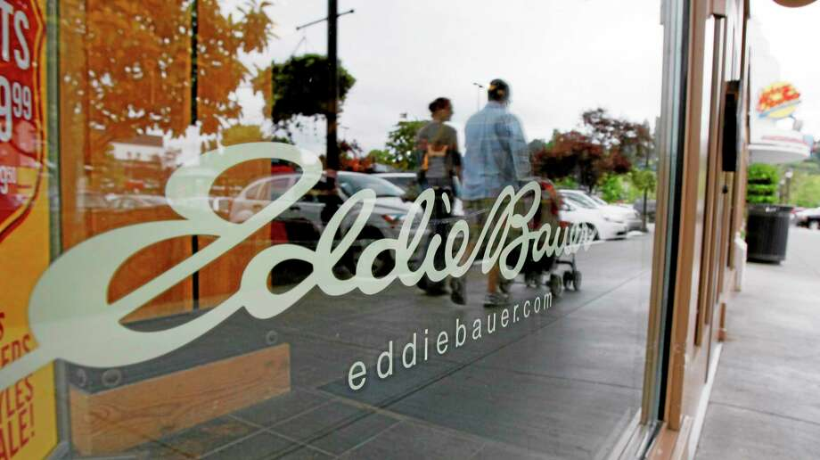 Shoppers are reflected in the window as they walk past an Eddie Bauer store in Seattle. Photo: Elaine Thompson — The Associated Press FILE   / AP