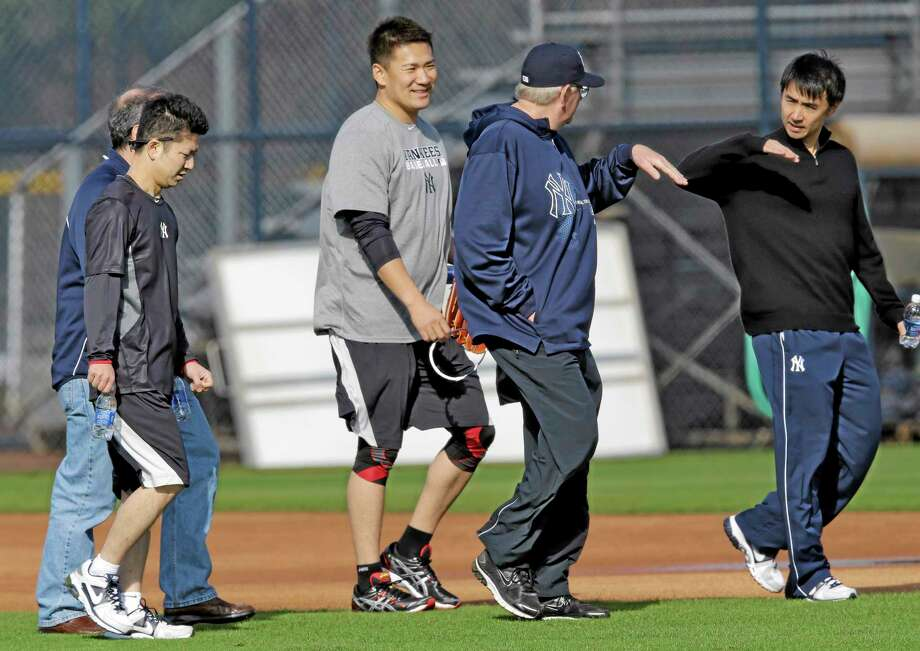 New York Yankees pitcher Masahiro Tanaka talks to pitching coach Larry Rothschild through interpreters during practice at the team's minor league facility Thursday in Tampa, Fla. Photo: Chris O'Meara — The Associated Press   / AP