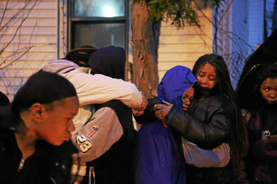 RICH SCINTO - NEW HAVEN REGISTER  Mourners take part in a vigil Friday night in New Haven following the slaying of a city teenager Thursday night. Photo: Journal Register Co.