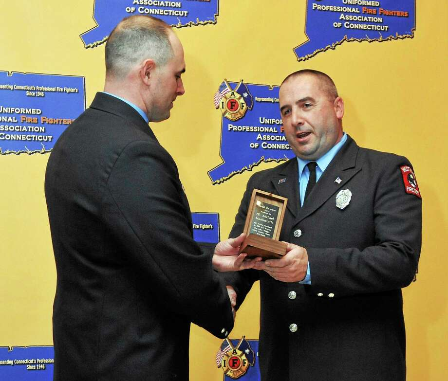 West Haven Firefighter Michael Southworth, right, is presented with the Medal of Merit by Firefighter John Perry Jr. during the inaugural citywide Service Recognition & Awards Ceremony Friday. Photo: Peter Casolino — New Haven Register