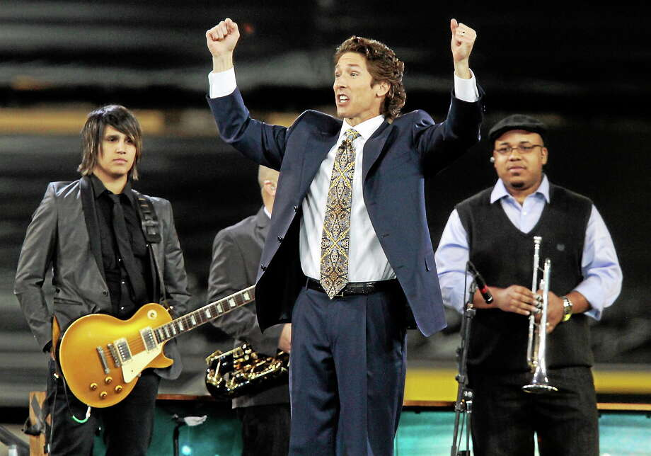 "Lakewood Church pastor Joel Osteen, center, leads his congregation in prayer during his ""A Night of Hope"" event at Dodger Stadium on Saturday April 24, 2010. Photo: AP Photo/Richard Vogel   / AP"