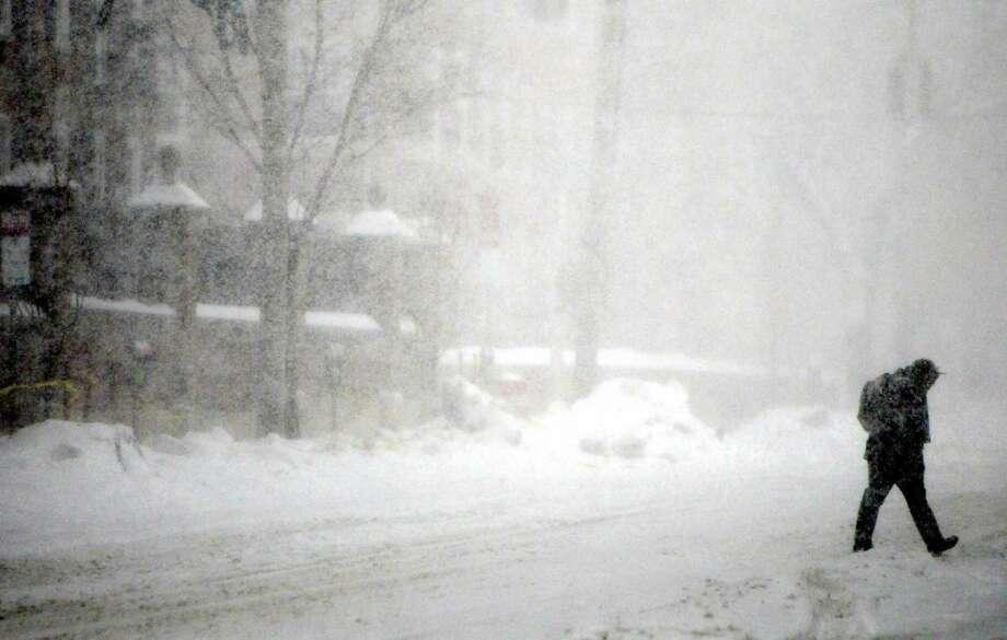 A lone pedestrian braves the heavy snowfall Thursday morning as he walks up Grove Street in New Haven. Photo: Peter Hvizdak — New Haven Register   / ©Peter Hvizdak /  New Haven Register
