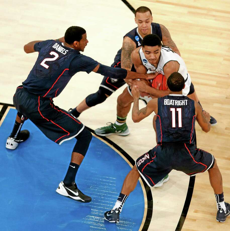 Michigan State guard Gary Harris, center, fights off UConn defenders Ryan Boatright (11), Shabazz Napier and DeAndre Daniels (2) during the second half of the Huskies' Elite Eight win on Sunday in New York. Photo: Julio Cortez — The Associated Press   / AP