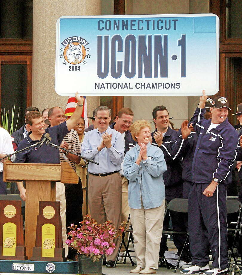 Geno Auriemma, left, and Jim Calhoun hold up a novelty license plate celebrating both the men's and women's national titles at a parade and rally in Hartford on April 18, 2004. Photo: Bob Child — The Associated Press   / AP2004
