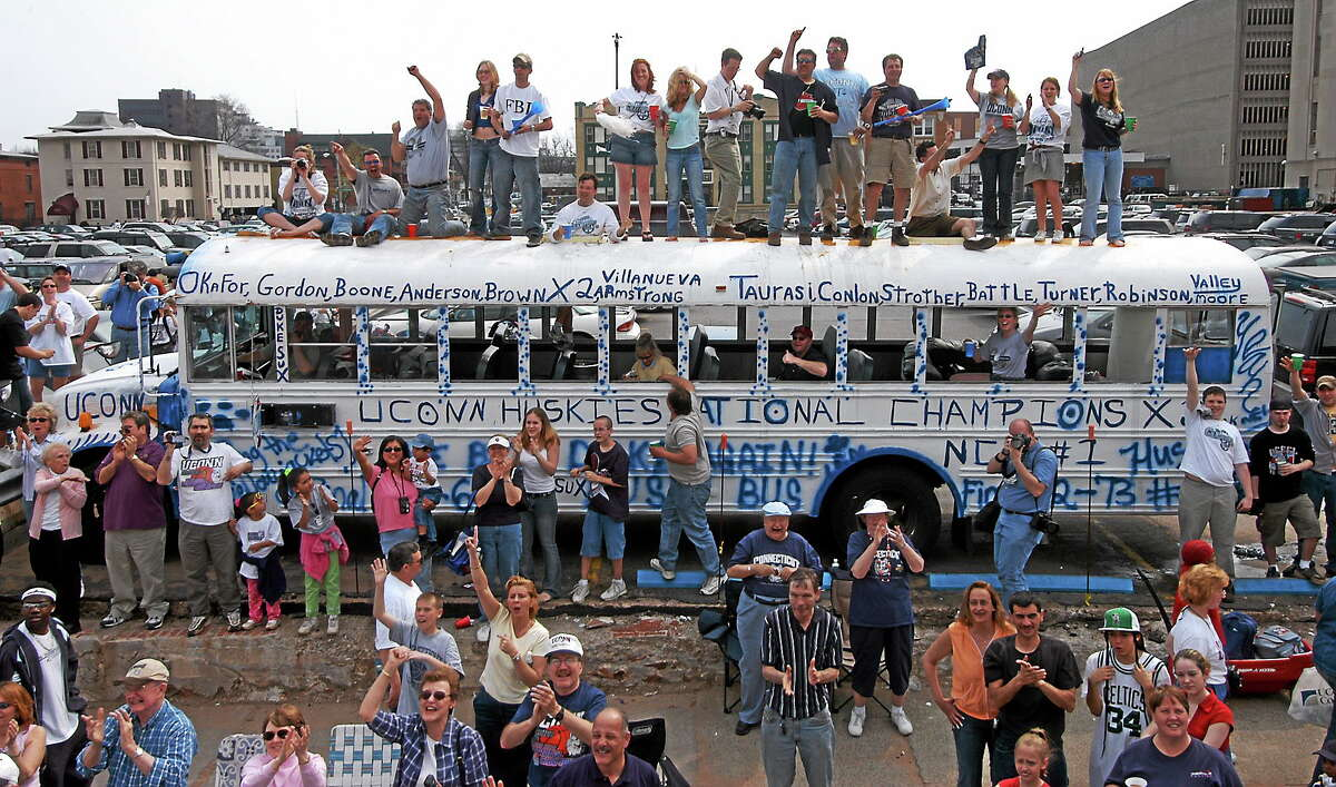UConn fans wave to the teams as they stand on top of a bus that they painted throughout the night during a joint parade in Hartford for the men's and women's college basketball national champions on April 18, 2004.